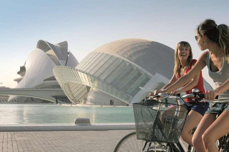 Unas turistas paseando en bici por la Ciudad de las Ciencias de Valencia