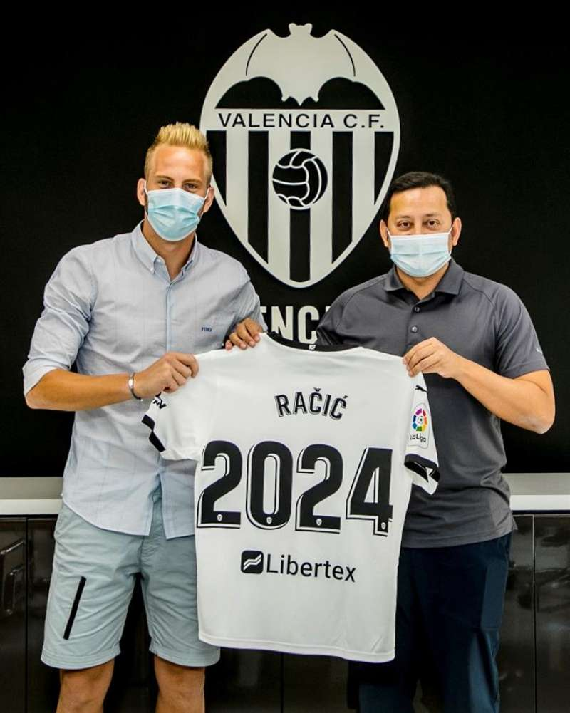El centrocampista serbio Uros Racic (i) posa junto al presidente, Anil Murthy, tras firmar su ampliacion de contrato hasta 2024. Foto cedida por el Valencia CF