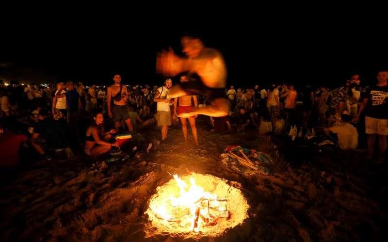 Un joven salta sobre una de las centenares hogueras de la noche de San Juan que arden en la playa del Postiguet. EFE