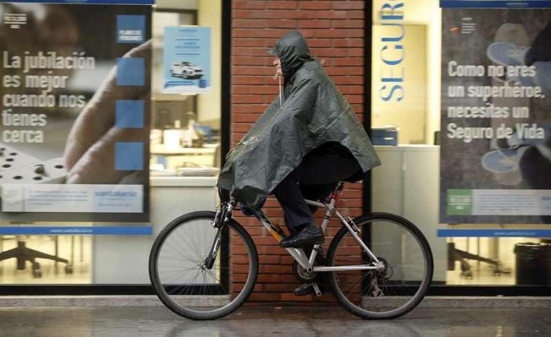 Un ciclista se protege del agua en un día lluvia en València. EFE/Juan Carlos Cárdenas/Archivo