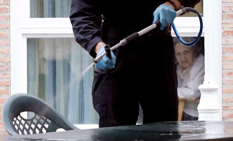 En Torrent, una anciana mira desde su ventana de la residencia mientras la UME desinfecta. EFE