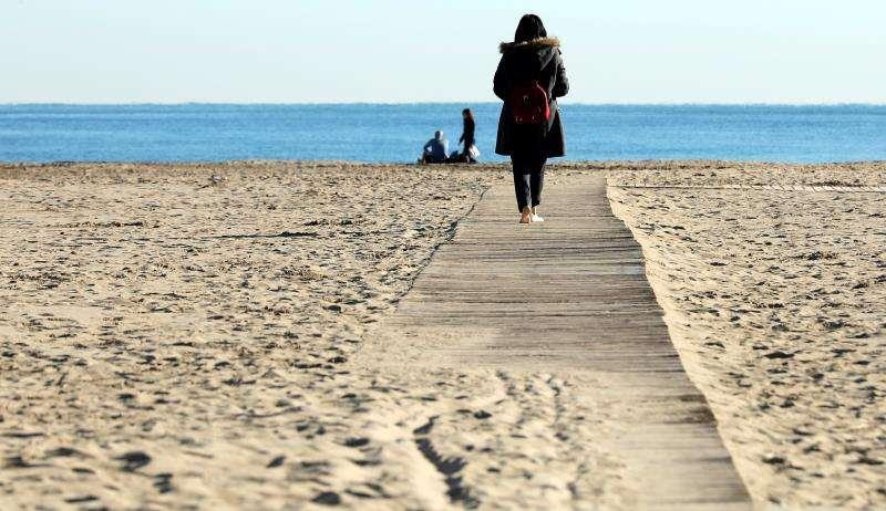 Una mujer pasea, abrigada, por la playa de la Malvarrosa de València. EFE/Archivo