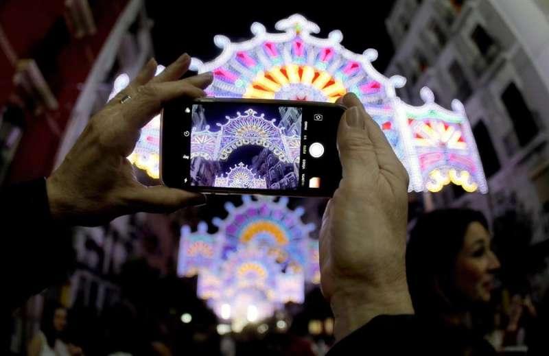 Una persona fotografía con su móvil el encendido de las iluminaciones falleras. EFE/Juan Carlos Cárdenas/Archivo