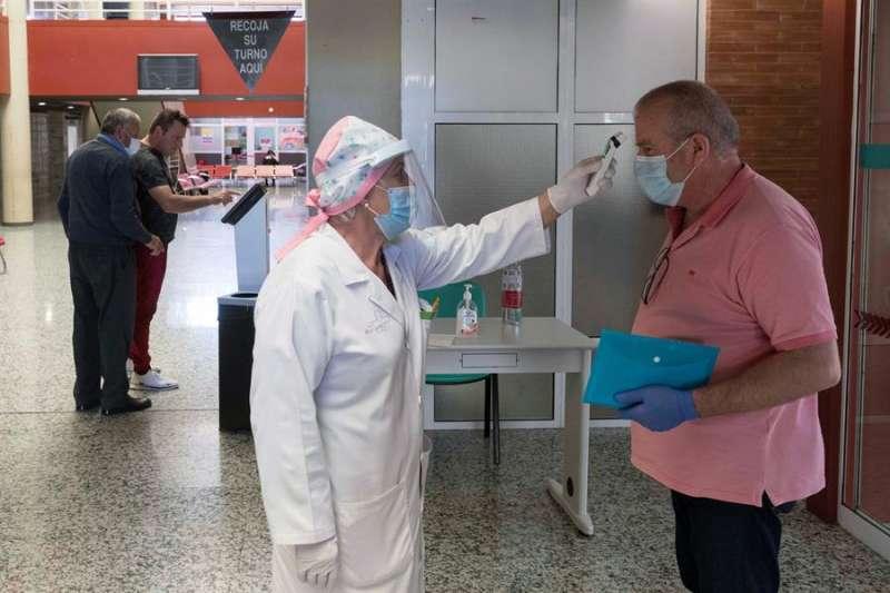 Una enfermera toma la temperatura a un paciente. E/Marcial Guillén/Archivo