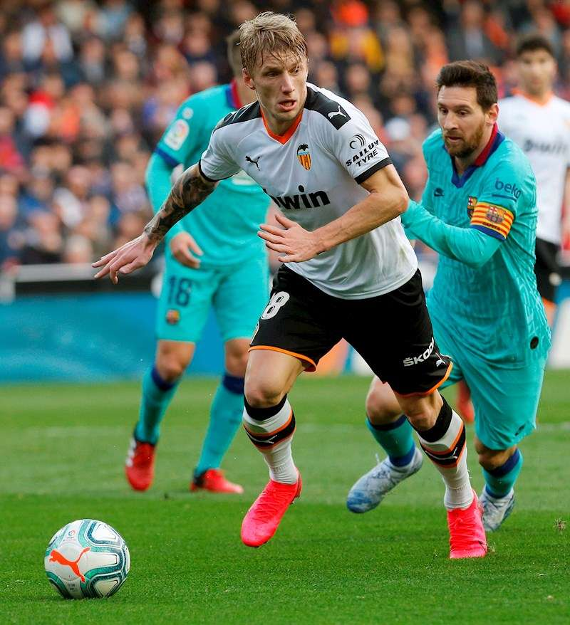 El centrocampista danés Daniel Wass (i) del Valencia, disputa el balón con el delantero argentino Lionel Messi del Barcelona (d). EFE/Archivo