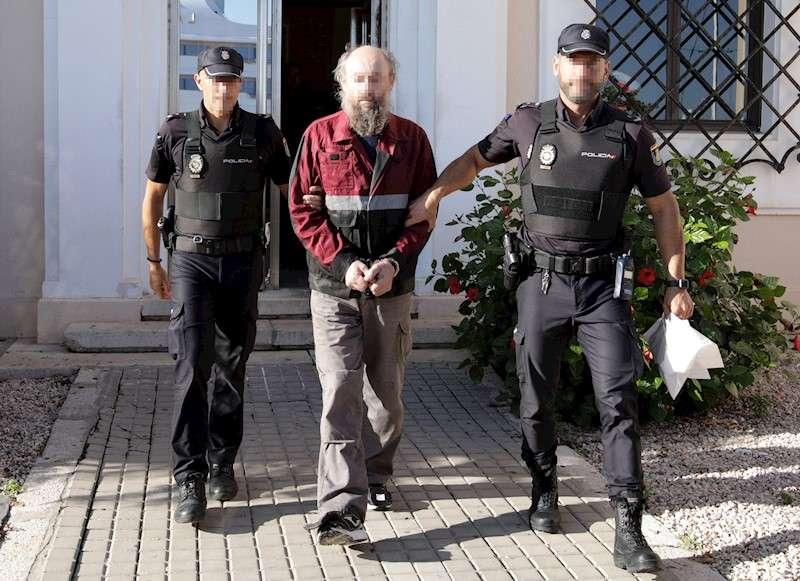 El ciudadano ruso de 54 años (c), presunto autor del degüello de su expareja sentimental de 44, es escoltado por dos policías desde la comisaría a los Juzgados de Denia (Alicante), este jueves, para ser interrogado por el juez. El sospechoso fue arrestado el martes tras presuntamente degollar a su expareja y compatriota, con la que tenía una orden de alejamiento. EFE/ Natxo Francés