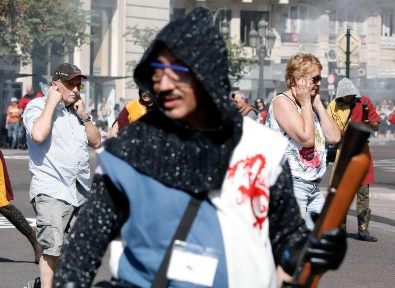 Dos turistas se tapan los oídos durante los disparos de trabuco del Alardo entre Moros y Cristianos. EFE/Juan Carlos Cárdenas/Archivo