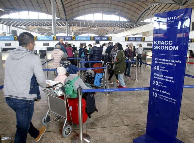 Pasajeros del aeropuerto de Alicante-Elche esperan a que se abra su mostrador y coger uno de los primeros vuelos tras la reapertura del aeródromo alicantino cerrado ayer por un incendio en su cubierta. EFE/MORELL