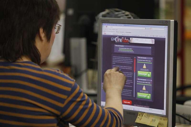 Una mujer consulta una página web que permite la descarga de películas y series de televisión a través de internet. EFE/Archivo