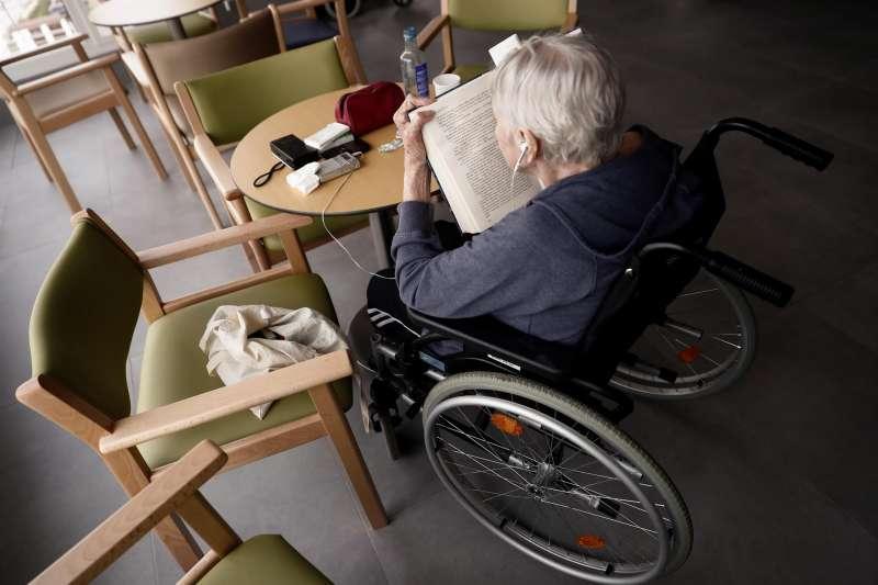 Una anciana lee un libro en una residencia.