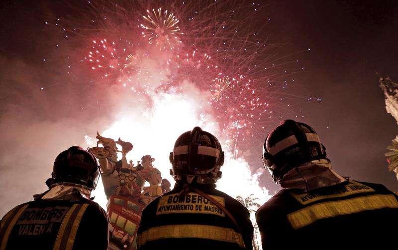 Miembros del cuerpo de bomberos observan un castillo de fuegos artificiales previos a la