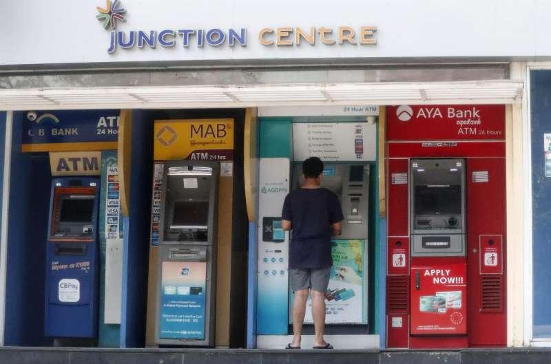 Una persona saca dinero de un cajero automático.