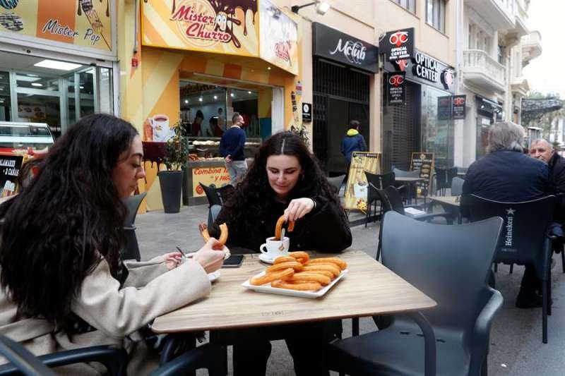 Dos jóvenes desayunan en una terraza del centro de Valencia. EFE