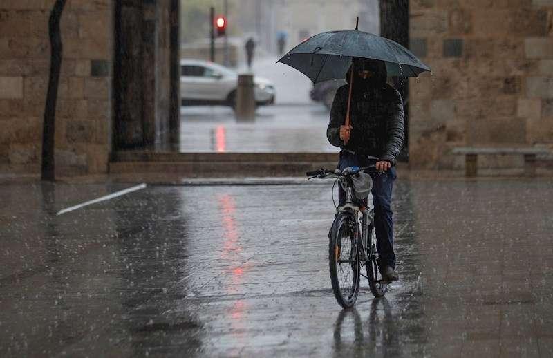 Una persona se protege de la lluvia en el centro de Valencia. EFE