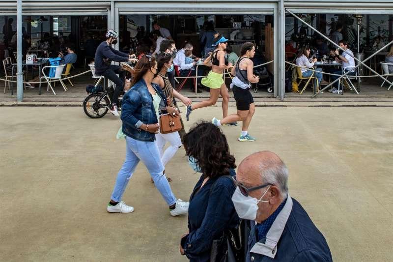 Varias personas pasean frente a un chiringuito del Paseo Marítimo de la Barceloneta hoy domingo, durante el primer día sin toque de queda en Cataluña. EFE/Enric Fontcuberta