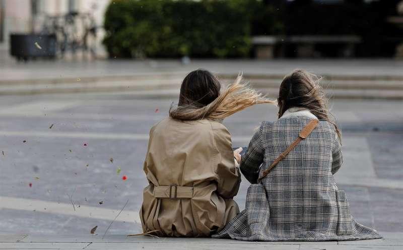 En la imagen, dos jóvenes charlan sentadas en un día ventoso. EFE/Manuel Bruque/Archivo