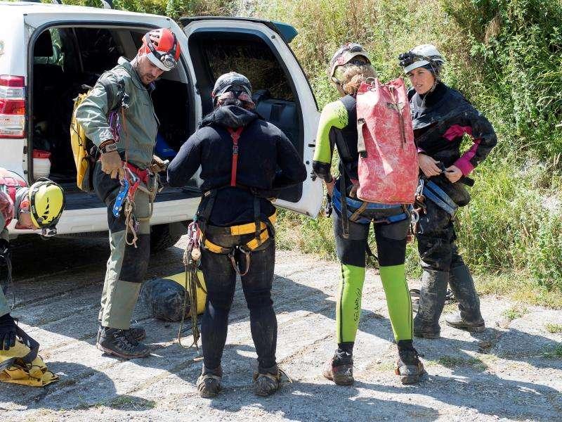 Las tres espeleólogas -dos de Barcelona y una de Vinaròs (Castellón)- tras su salida de la cueva, acompañadas de los miembros del GREIM y agentes de la Guardia Civil. EFE