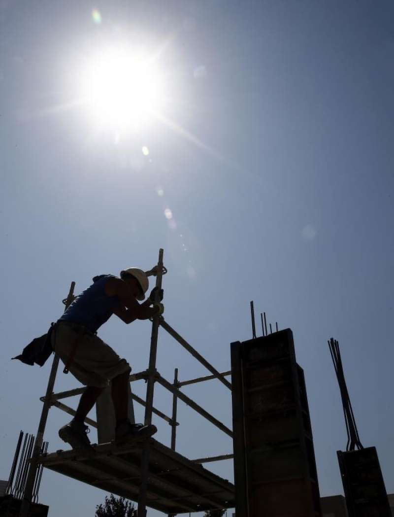 Un obrero trabaja en un edifico en construcción bajo un intenso sol.EFE/Archivo