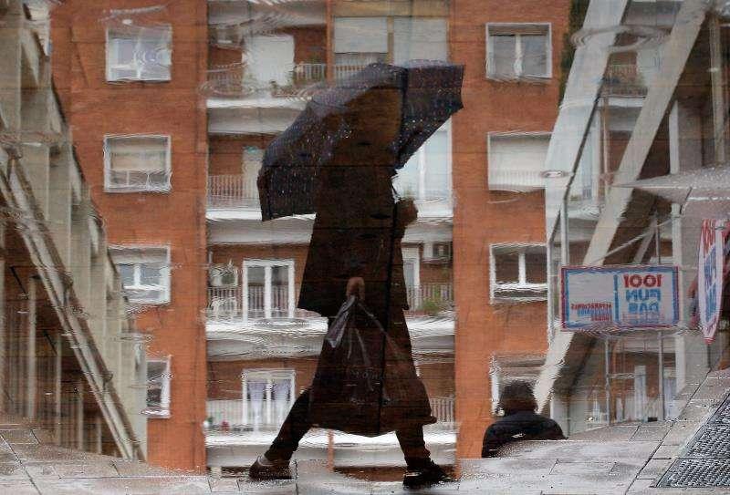 Un persona se resguarda de la lluvia bajo un paraguas. EFE/Archivo