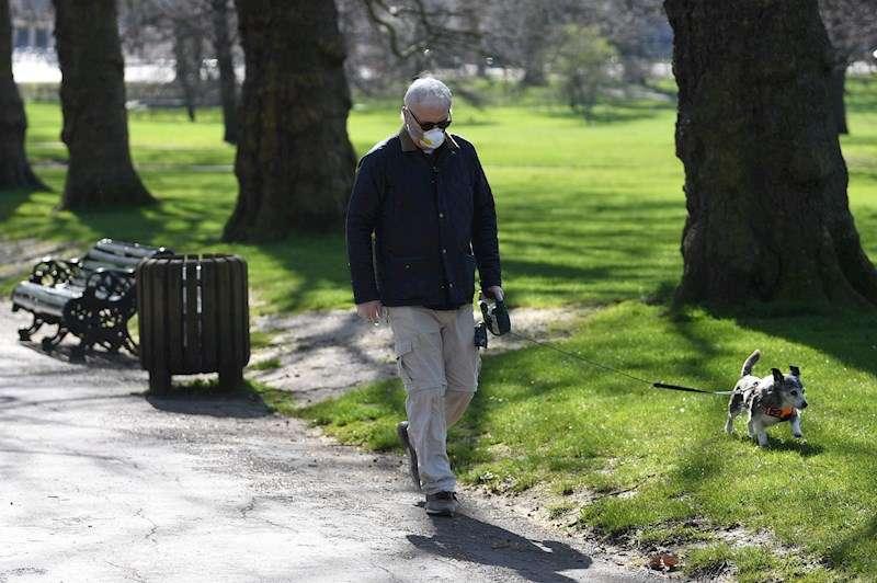Una persona paseando a su perro por un parque. EFE