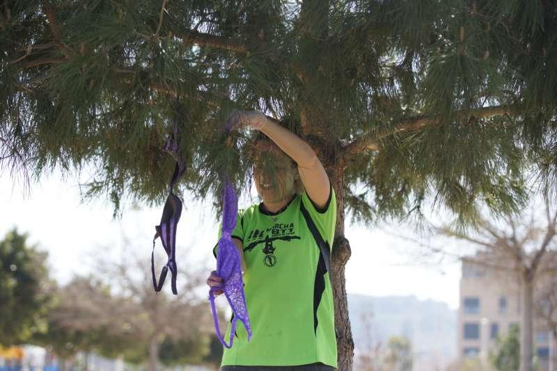 Una mujer colgando un sujetador morado en un árbol de Sagunt. EPDA