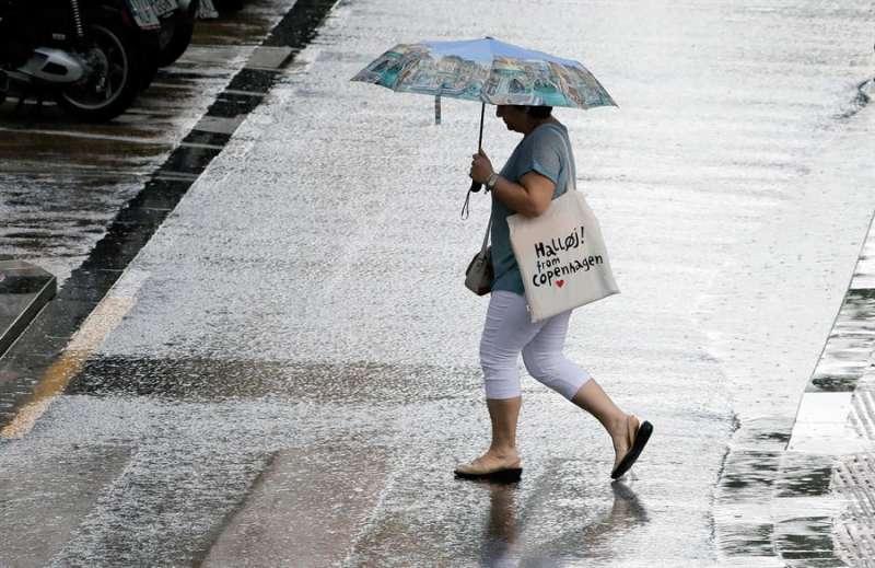 Una persona se resguarda de la lluvia con el paraguas. EFE/ Juan Carlos Cárdenas