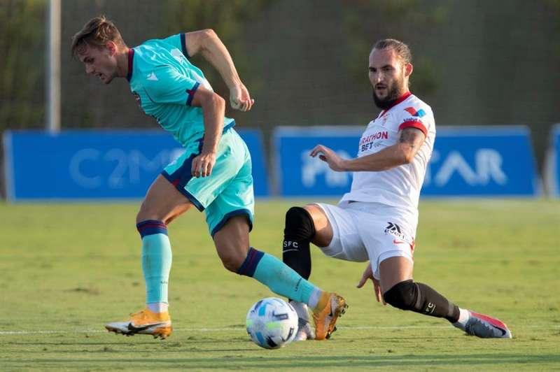 El centrocampista serbio del Sevilla FC Nemanja Gudelj (d) lucha por el balón con Dani Gómez (i), del Levante Unión Deportiva, este martes durante el partido amistoso en el estadio del Pinatar Arena. EFE/Marcial Guillén