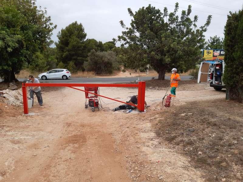 Trabajadores municipales instalando una barreras para cerrar un camino en Paterna. / EPDA