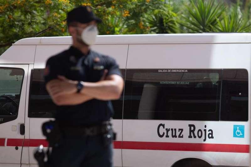 Un agente de la Policía Nacional delante de una ambulancia. EFE/Archivo