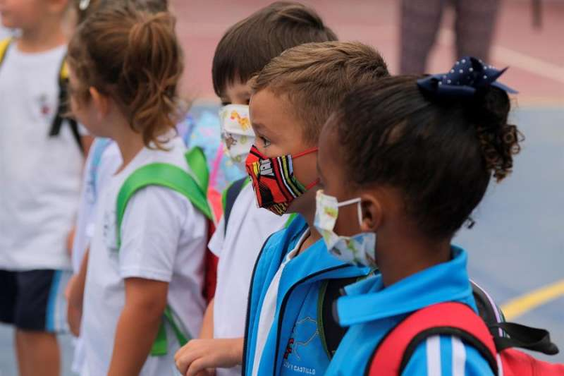 En la imagen, varios niños esperan para entrar a su clase, entre señalizaciones y medidas de desinfección. EFE
