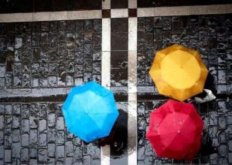 Tres personas se protegen de la lluvia con sus paraguas. EFE
