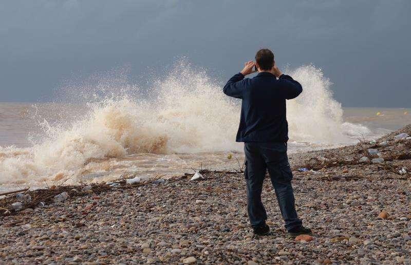 Una persona fotografía el oleaje de la playa, esta mañana en Castellón. EFE