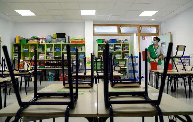 Una trabajadora del servicio de limpieza desinfecta las sillas y los pupitres de una clase de infantil de Valencia. EFE