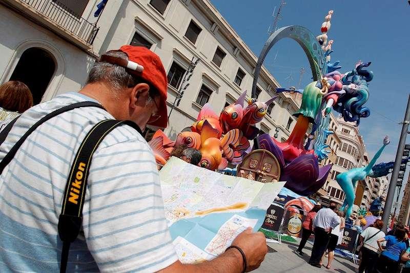 Un turista consulta un mapa ante una hoguera de Alicante. EFE