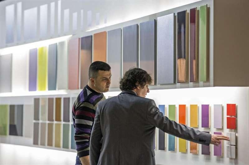 Un vendedor muestra a un cliente unos diseños de material cerámico en la feria de pavimentos cerámicos Cevisama. EFE/Manuel Bruque