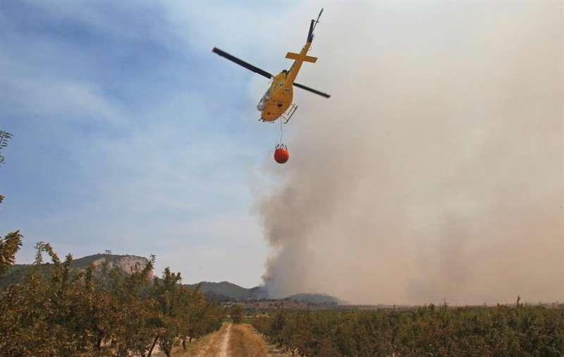 Imagen de archivo de un helicóptero durante la extinción de un incendio forestal.EFE/Pep Morell