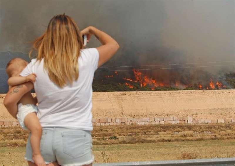 Una mujer observa el incendio forestal entre Monóvar y La Romana. EFE