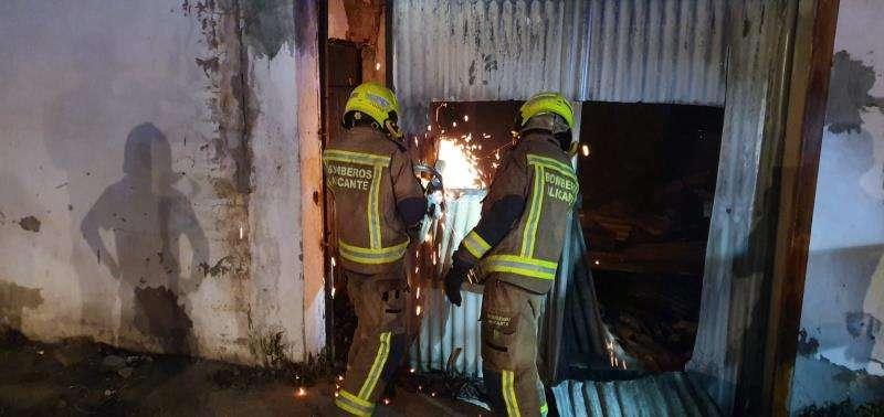 Dos bomberos trabajan en la extinción de un incendio en una nave con vehículos en Alicante. EFE/Ayuntamiento Alicante