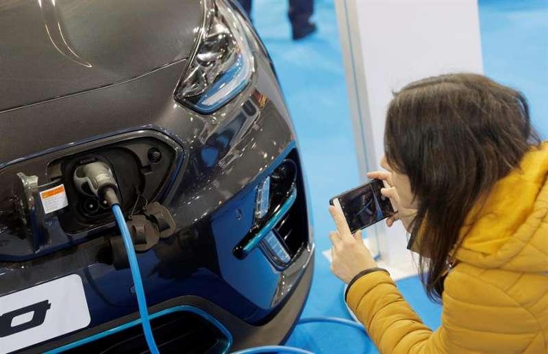 Una persona contempla la toma de corriente de un vehículo eléctrico en la Feria del Automóvil de València. EFE/Kai Försterling/Archivo