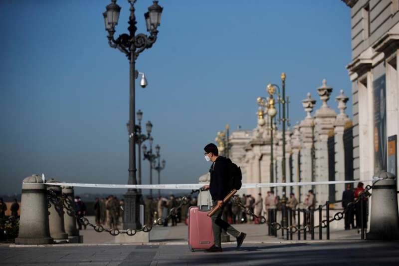 Un joven con su maleta pasa ante el Palacio Real de Madrid. EFE/ Juan Carlos Hidalgo/Archivo