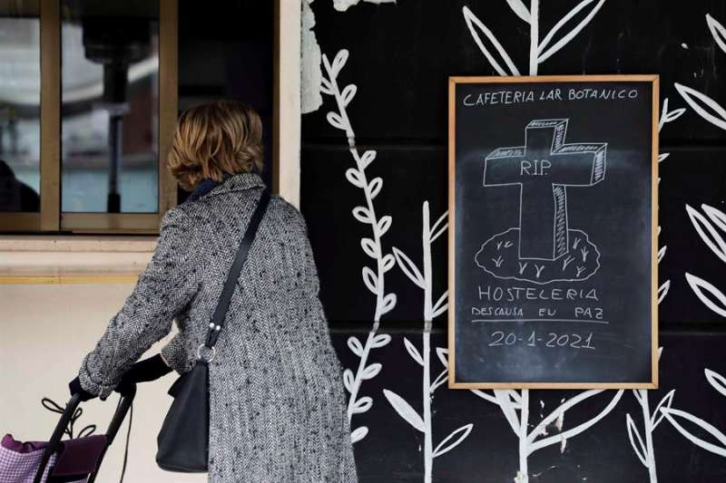 Una mujer observa el cartel de una cafetería. EFE