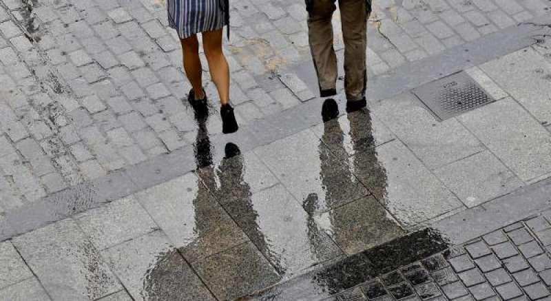 Dos personas caminan bajo la lluvia. EFE/Manuel Bruque/Archivo./ EPDA