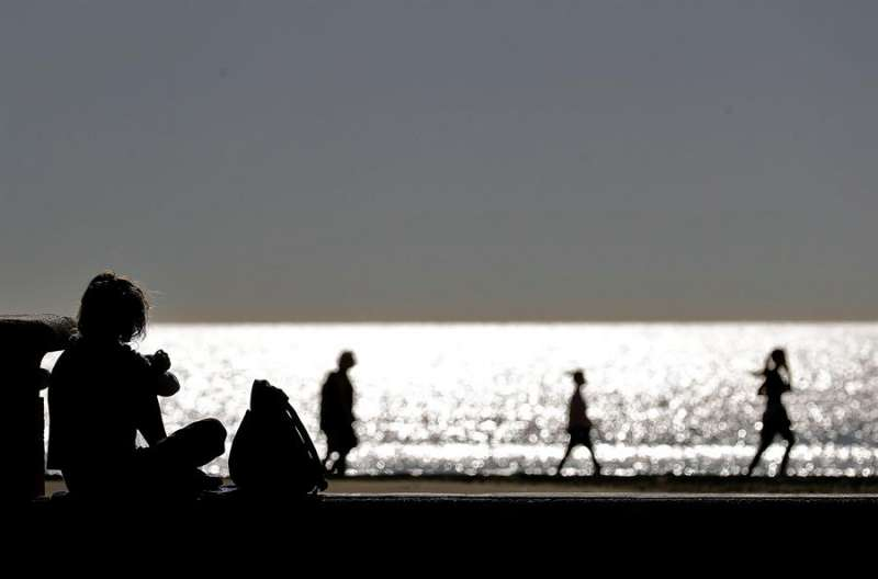 Varias personas disfrutan de un paseo a primera hora en la playa de la Malvarrosa en el horario establecido tras no haber pasado a la Fase 1. EFE/Manuel Bruque