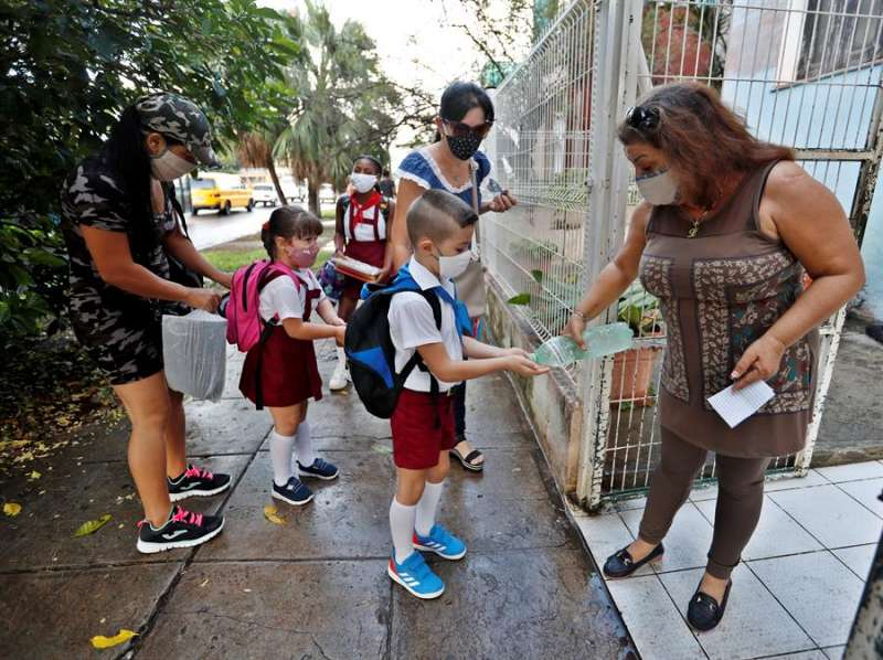 na educadora (d) desinfecta las manos de los estudiantes al llegar a la escuela. EFE/Yander Zamora