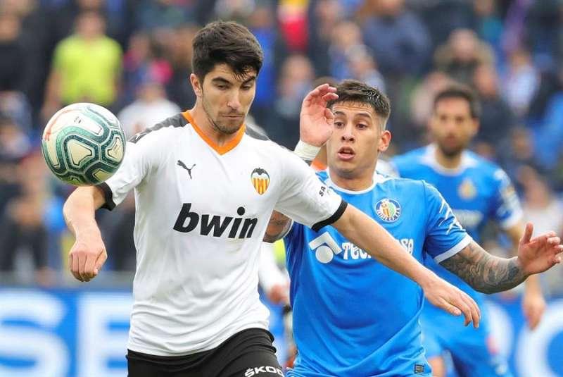 El centrocampista Carlos Soler (i) del Valencia disputa el balón a un rival. EFE