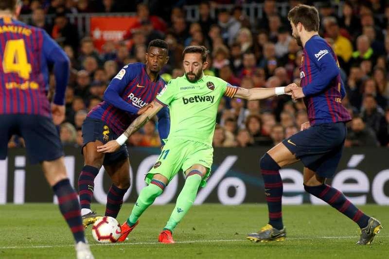 El delantero del Levante UD José Luis Morales (c) intenta rematar ante Nelsón Semedo (i) y Gerard Piqué, del Barcelona, durante un encuentro anterior entre ambos equipos en el estadio del Camp Nou, en Barcelona. EFE/Quique García.