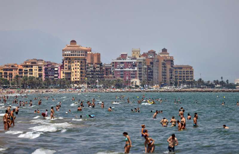 Cientos de personas disfrutan del baño en la playa de La Patacona en Alboraya (Valencia).