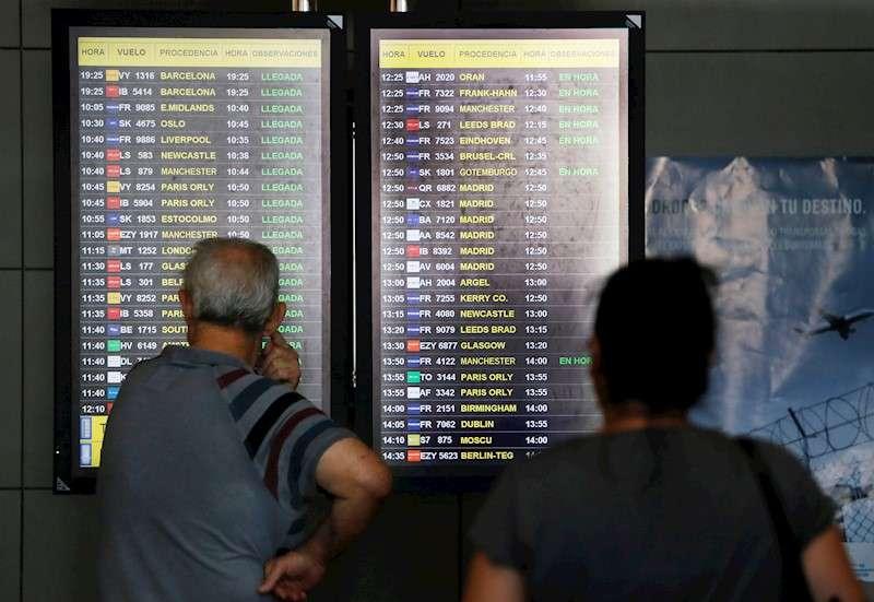 Dos viajeros observan un panel informativo de vuelos en el aeropuerto de Alicante. EFE/Manuel Lorenzo/Archivo