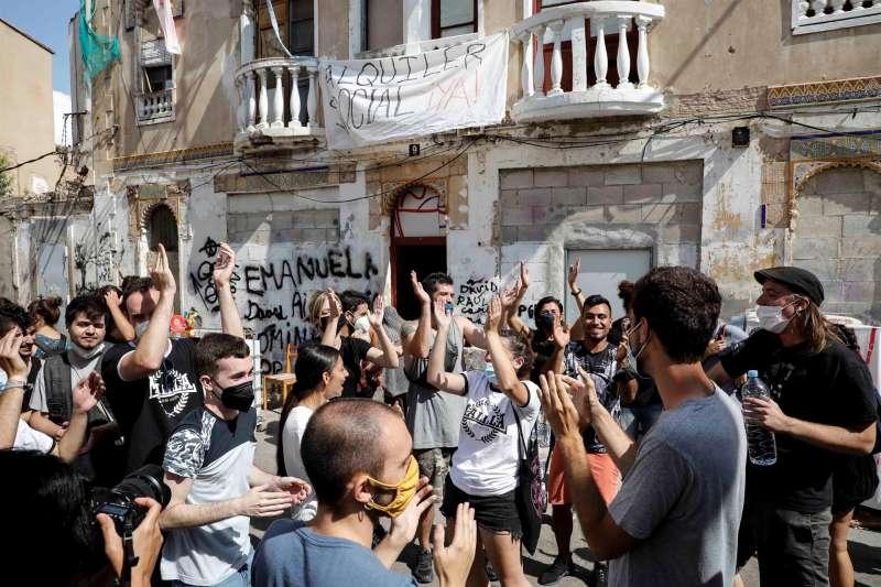 Varias personas corean consignas mientras se concentran a las puertas de un edificio que iba a ser desalojado este lunes en el barrio de la Cruz Cubierta de Valencia.