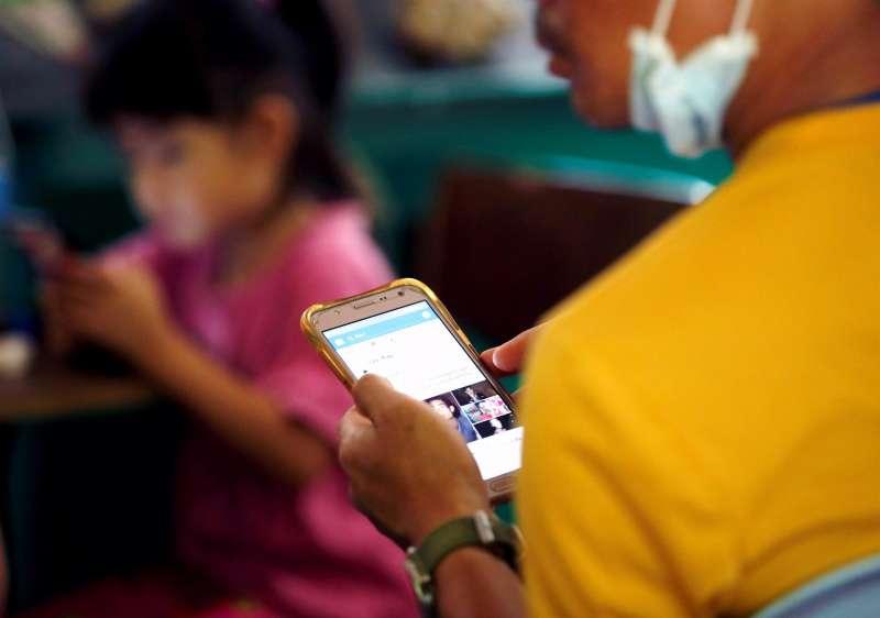 Un joven y una niña consultan en su casa sendos teléfonos móviles durante la pandemia. EFE